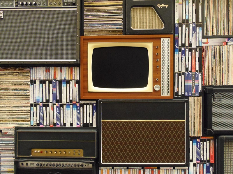 Analog TV set surrounded by VCR cassettes.